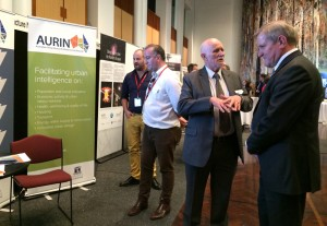 The Hon Ian Macfarlane MP, Minister for Industry, learns about AURIN from Prof Bob Stimson at the NCRIS Showcase