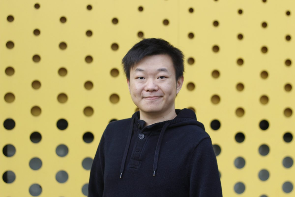 Image of Asian man wearing black hoodie standing in front of yellow background with black circles on it